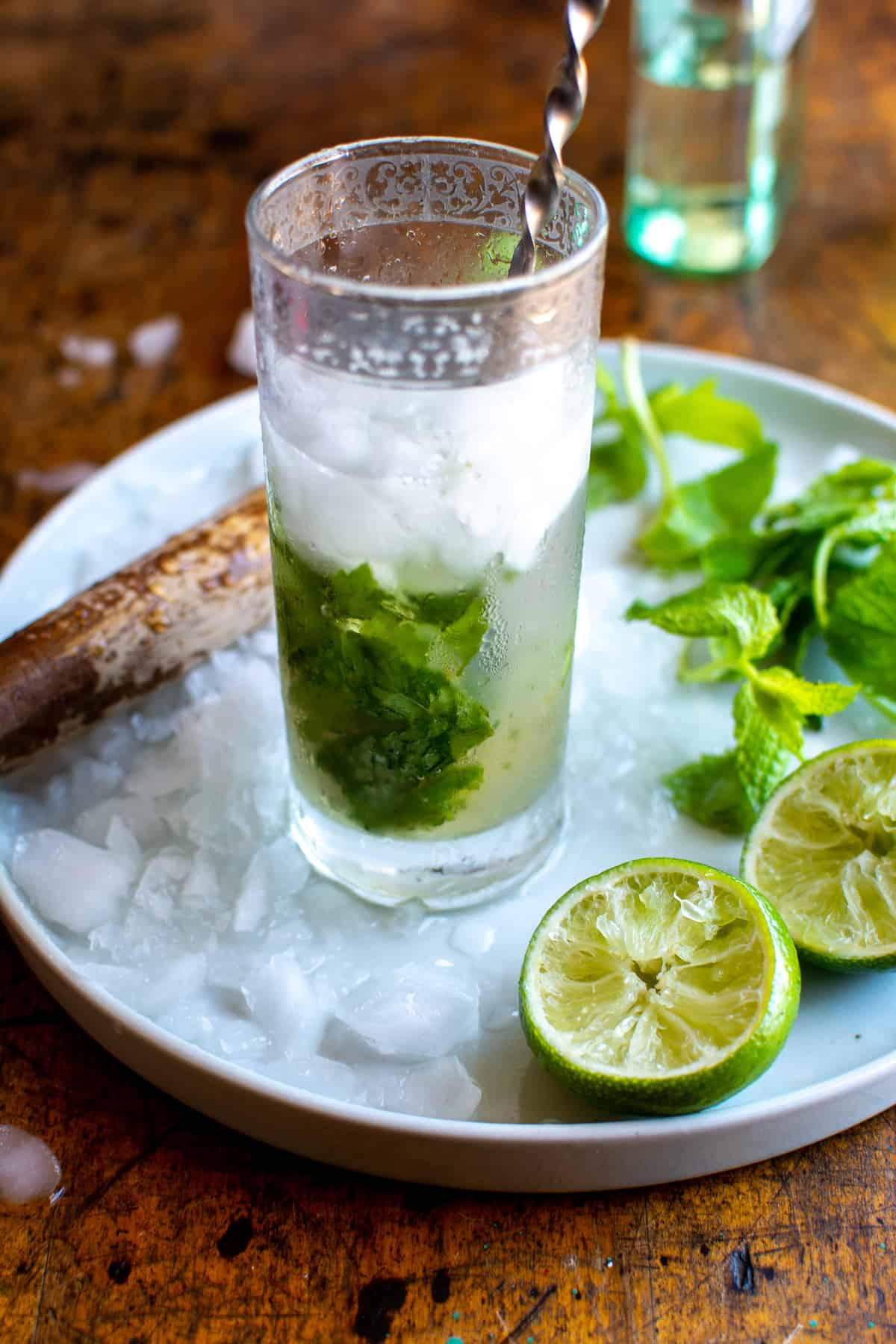 A mojito in a tall glass filled halfway with ice sitting on a white plate next to a lime that has been squeezed.