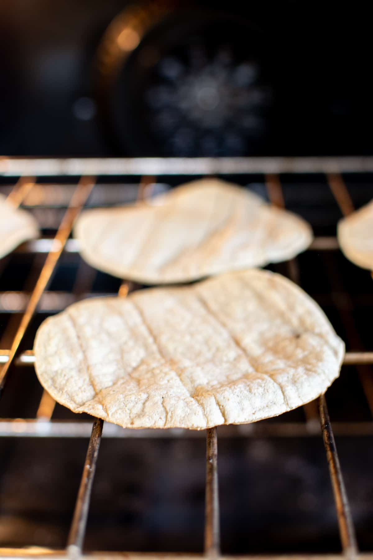 Baked tostadas sitting directly on the oven rack in the oven.