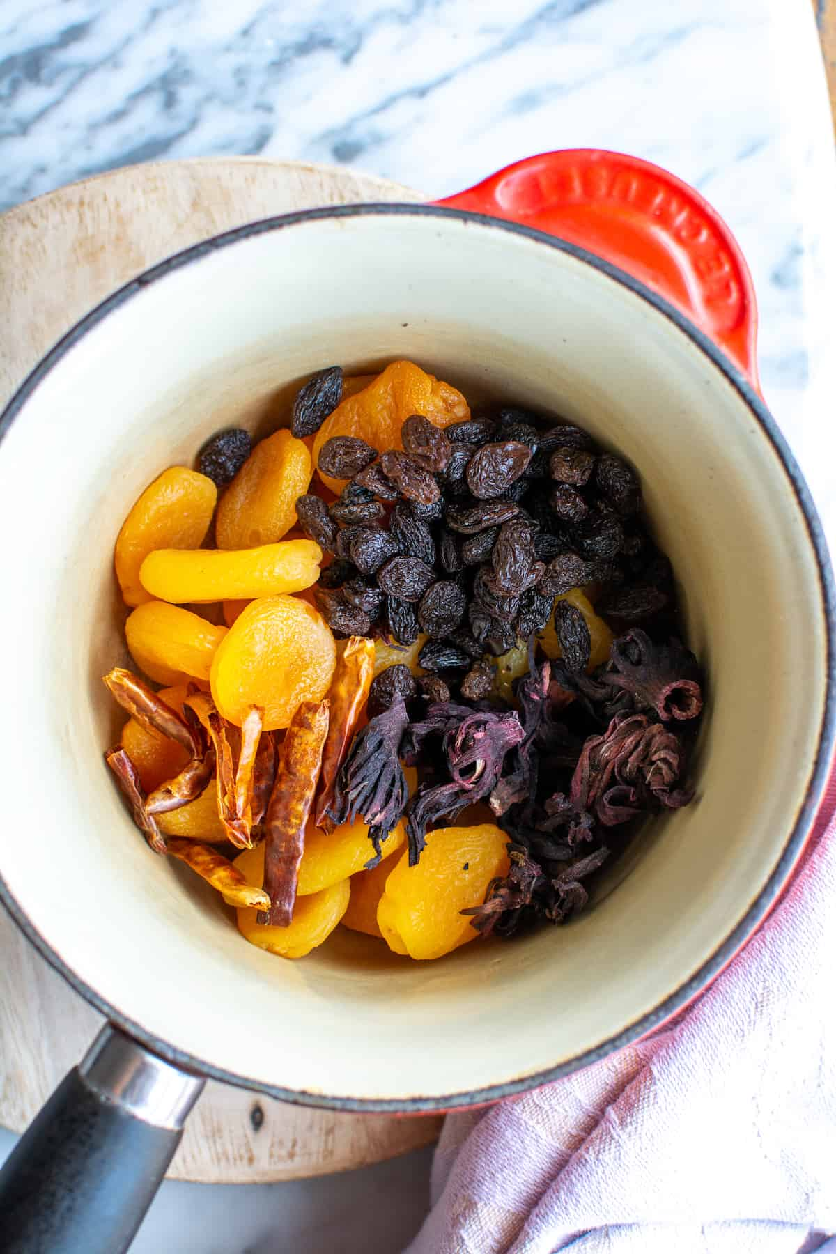 A saucepan filled with arbol chiles, dried apricots, hibiscus flowers, and raisins.