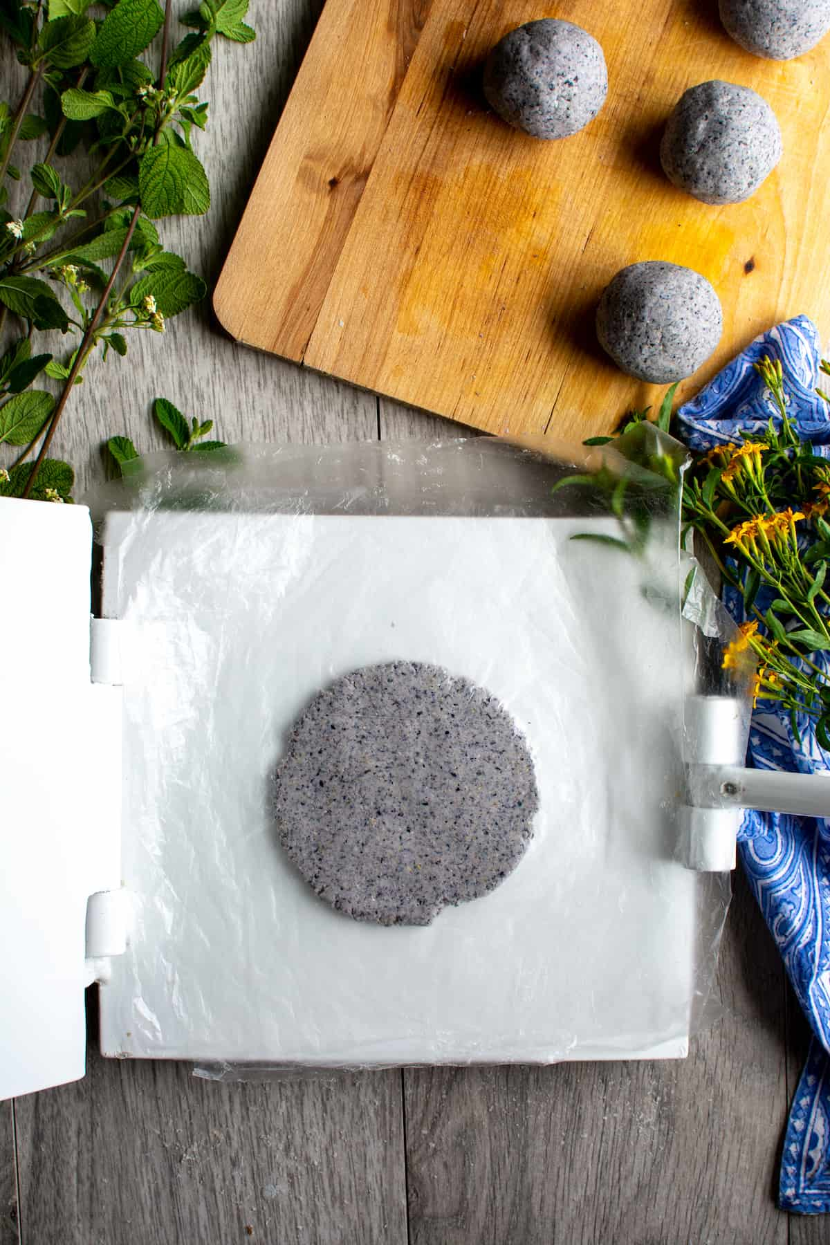 A flattened round of blue corn masa on a white tortilla press next to several other balls of blue corn masa sitting on a wood cutting board.