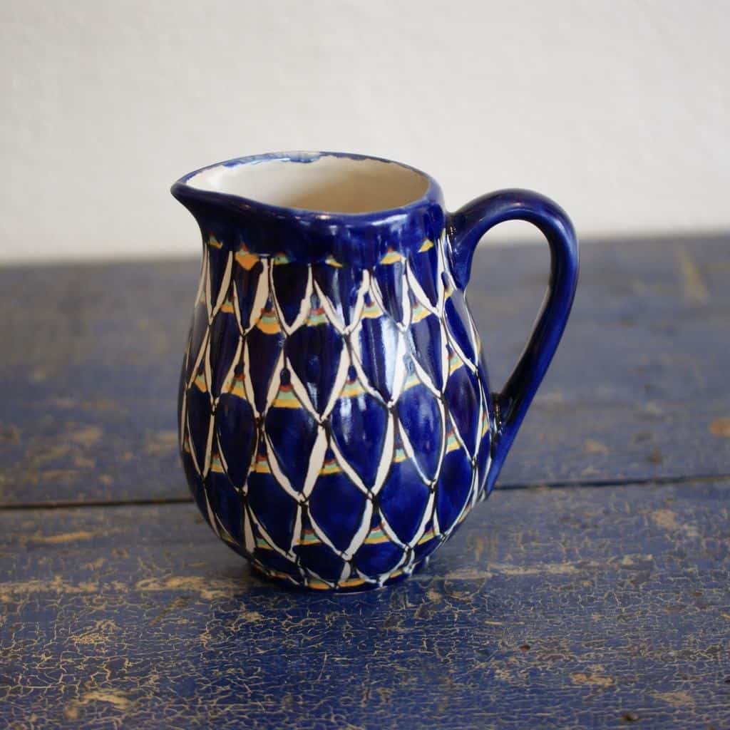 A small blue Talavera pitcher with a triangle pattern and green, brown, and yellow stripes sitting on a wood table.