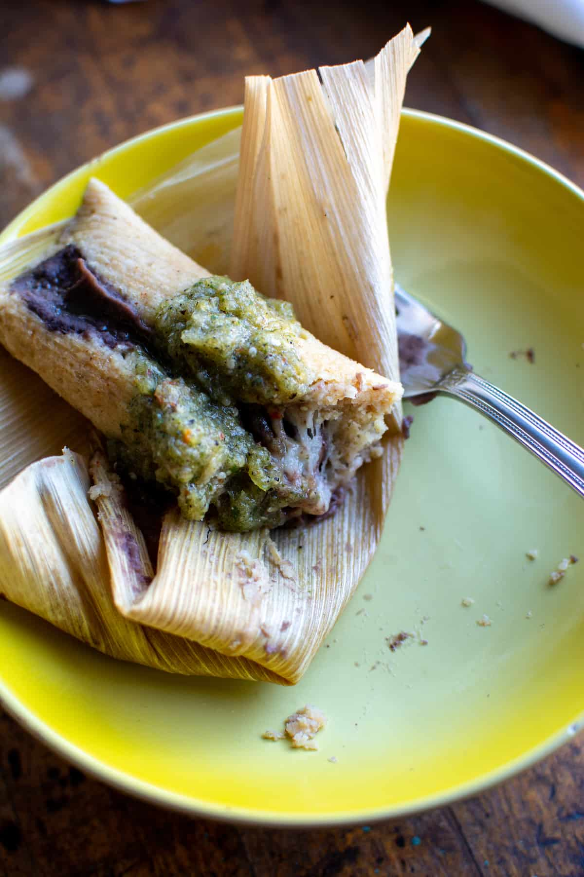 A black bean and cheese tamal sitting on a yellow plate that has been half eaten there is a fork sitting to one side.