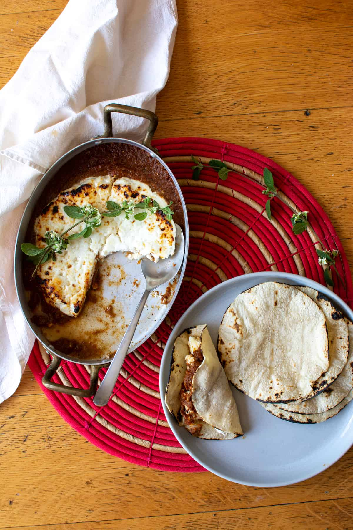A copper dish of baked Panela cheese with red salsa sitting next to a plate of toasted corn tortillas with one taco made from the Panela cheese.
