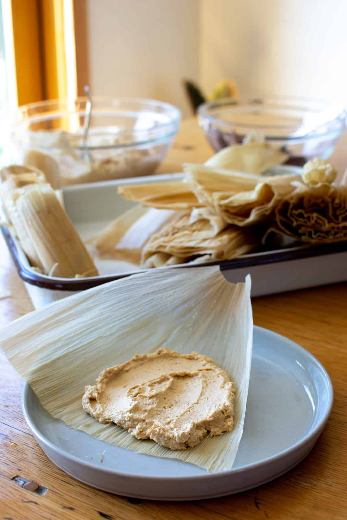 A corn husk sitting on a white plate on a wood table with masa dough spread over it and a white dish of corn husks in the background.