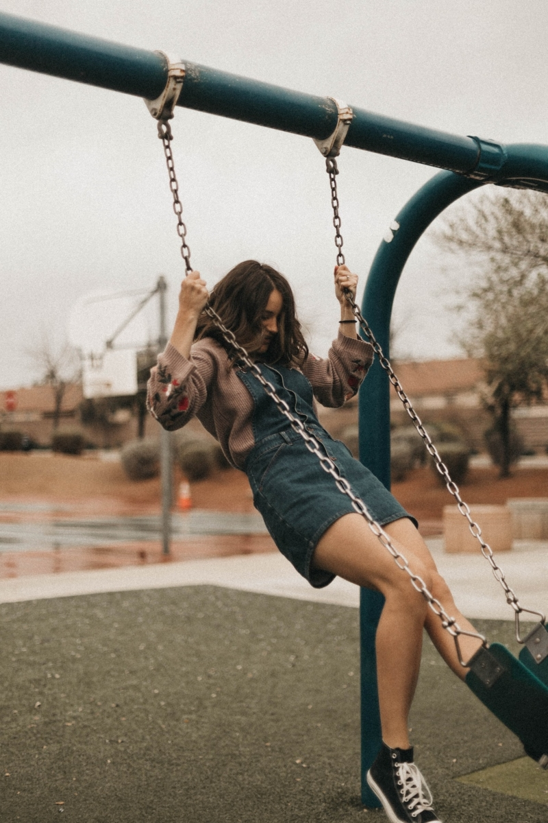 Young woman playing on swings