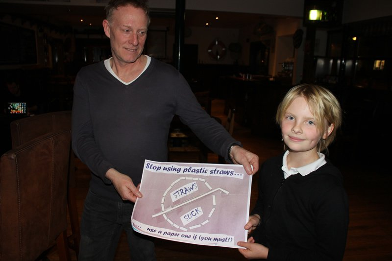An Ullapool schoolchild with a poster promoting the #NaeStrawAtAw campaign