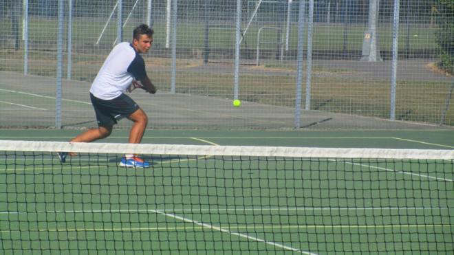 Ragazzo gioca a tennis in Inghilterra