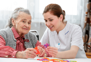 Caregiver working with older woman to complete a puzzle