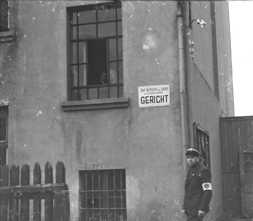 https://i0.wp.com/www.holocaustresearchproject.org/ghettos/judenratgal/A%20Jewish%20policeman%20stands%20guard%20outside%20the%20ghetto%20courthouse.jpg