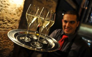 A waiter carrying a tray of wine at the launch of Edinburgh wine bar, Divino Enoteca is shown in a PR photograph