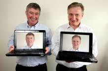 Two men with their faces on their laptop screens