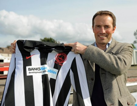 Banks Renewables director Colin Anderson poses with a Cumnock Juniors shirt with his company logo on the front