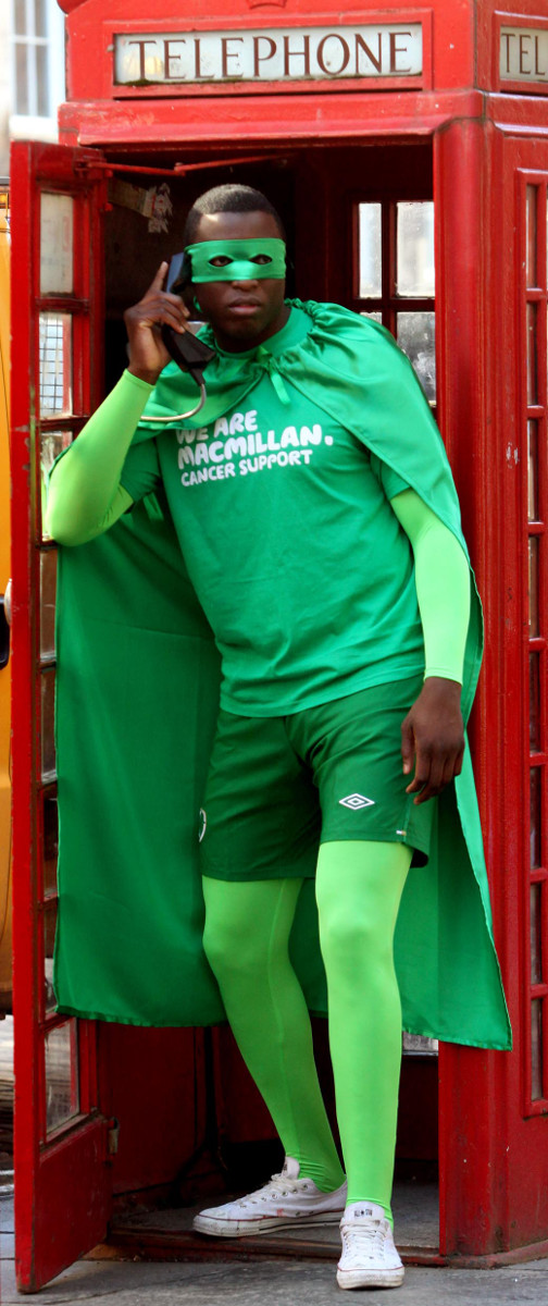 A man dressed like a superhero in a green cape bursts from a telephone box