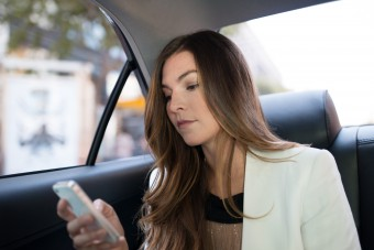 A female passenger using the Uber app in the back of an Uber car
