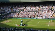 Women playing tennis on Wimbledon centre court to illustrate a blog post by a public relations agency