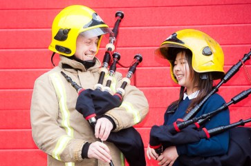 Firefighters, Steven Walls, tries his hand at the pipes with Yin Chen, from Riverside school, at Govan Fire Station