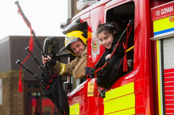 Fire fighter and child in fire engine with bagpipes