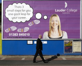 A man walking past a billboard advert for Lauder College