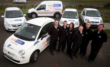 Euro Business Team next to vans and cars