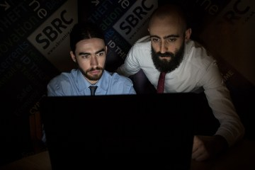 Two men in suits look at a computer screen in a dark room