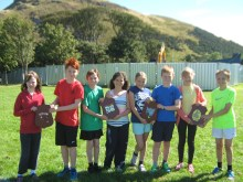Eight children stand with four plaques in a green field.