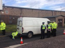 Image of Police Officers and white van on the road, with one officer checking underneath the van