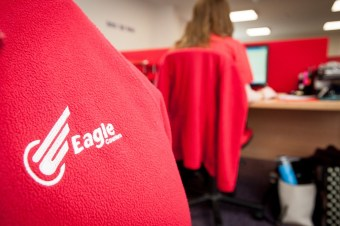 Close up of red cardigan with Eagle Couriers logo on in white. Office background with the back of someone on a computer.