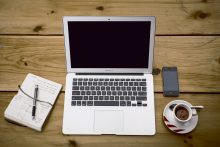 Image of an open notebook and pen, MackBook Air, iPhone and cup of tea and spoon on a saucer.