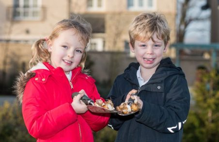 Close-up PR Photo of two of the kids from Ratho Primary School with trowels full of bulbs