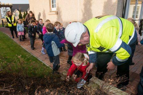 PR Photos of the kids and CALA Representative planting the daffodil bulbs