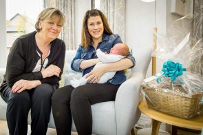 PR Photography CALA Homes Sales Advisor, Jenny Thomson sits with new mother, Rosie with her baby Lachlan