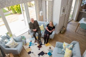 Councillor Ricky Henderson sits comfortably in the Kinleith Showhome with CALA Representative as viewed from the stairs by PR Photography