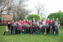A photo of a large group of children from St Margaret's RC Primary school with gardening equiment - spades, rakes, gloves, watering cans and a wheelbarrow for Photography PR