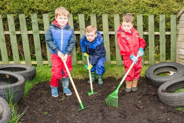A picture of three young boys raking the earth