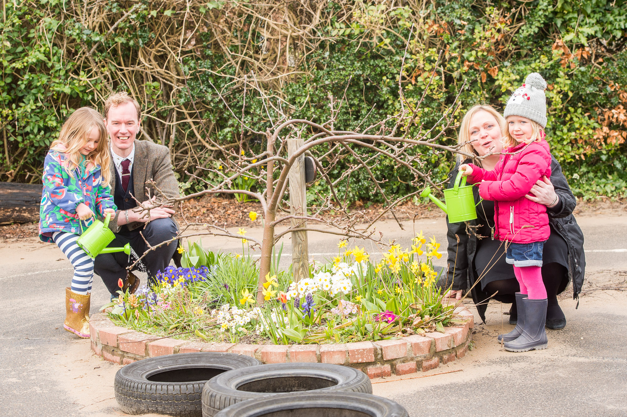 A photo of two young girls with a man and a woman watering a flower bed for Photography PR