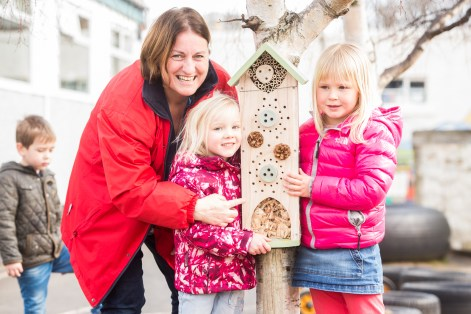 A photo of two young girls and a woman posing next to an insect house for Photography PR