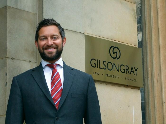 Glen Gilson, Managing Partner at Gilson Gray, stands in front of Gilson Gray sign - Legal PR