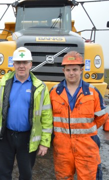 A photo of the deputy site manager and the plant mechanic wearing hard hats and high-vis jackets standing in front of a large yellow digger.