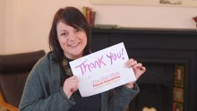 An image of Roslyn Neely, CEO of Sick Kids Friends Foundation holding a thank you sign and smiling