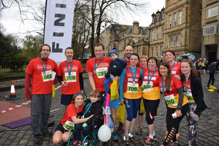 An image of marathon runners at the end of their race gathered with Ruby as a part of a Care PR story