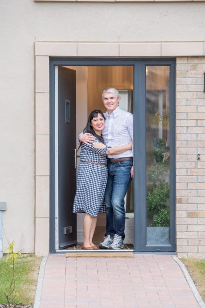Robert and Jennifer pose in the doorway of their new home
