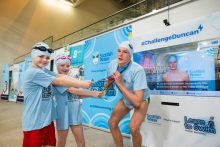 A public sector PR photo of two kids trying to steal Duncan Scott's medals from round is neck at the launch of the virual swimming game Challenge Duncan