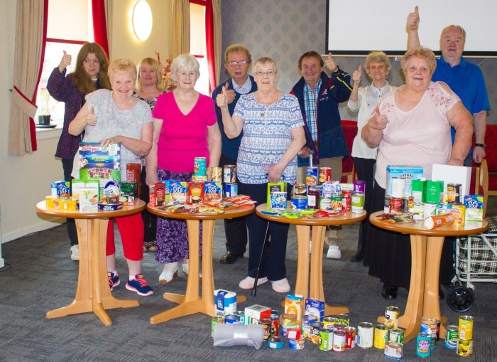 Care PR photograph of tenants at a Greenock retirement development collecting donations for a local food drive