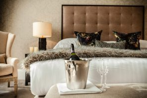 A bottle of champagne and two glasses pictured in front of a bed in a hotel PR photograph