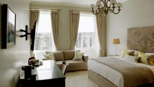 Hotel PR photograph of an elegant, bright bedroom at Nira Caledonia