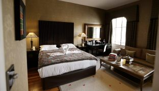 Hotel PR photograph of a romantic bedroom at Nira Caledonia with towel swans and rose petals on the spacious bed
