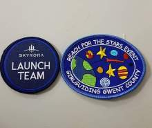 Two space badges are pictured in a tech PR image taken at a workshop to inspire young Brownies in Wales