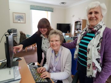Charity PR photograph of Bield tenants experiencing the world of IT.