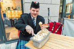Piper Robert Reid scooping Mackie's Haggis and Marmalade Ice cream in a Food and Drink PR photo for Burns Night
