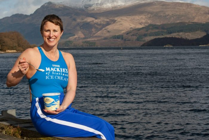 Food and Drink PR Photo of Ice Swimmer Jade Perry at Loch Lomond at a Luss in her swimming costumer eating tub of Mackie's Ice Cream